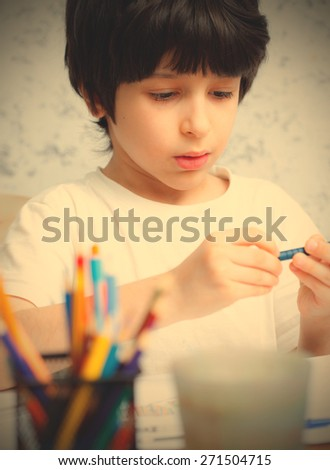 boy chooses a pencil for drawing.