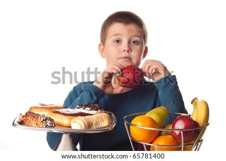 boy choosing a healthy apple snack over a dessert - stock photo