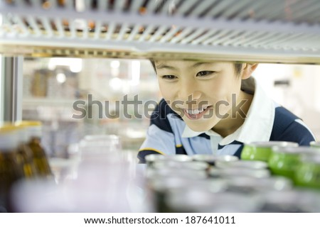 boy choosing drink at convenience store - stock photo