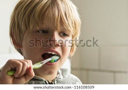 Boy cleaning teeth - stock photo
