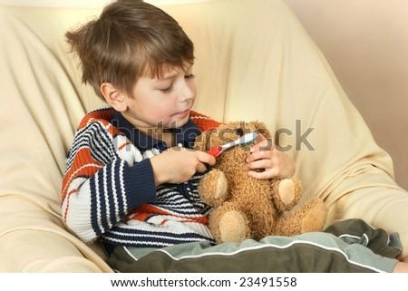 Boy cleans teeth his teddy bear - stock photo