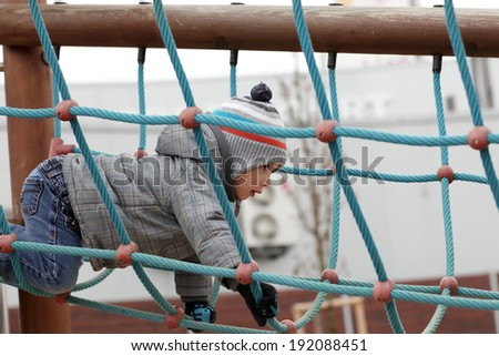 Boy climbing on rope at outdoor playground - stock photo