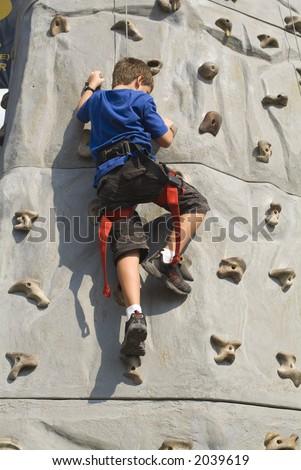 Boy climbing rock wall series - stock photo