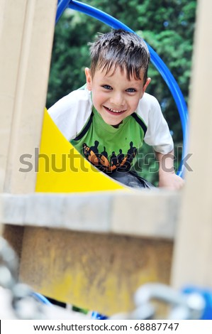 boy climbing wall bars on the playground - stock photo