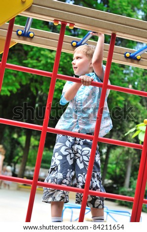 boy climbing wall bars on the playground