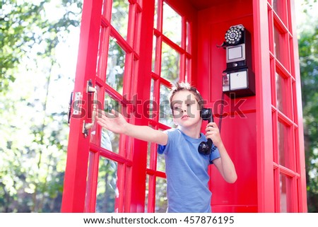 boy closes the door of the red telephone booth.boy talking on the phone in a red phone box and closes the door that opened a gust of wind. scared kid - stock photo