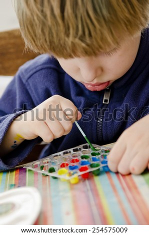 boy colors the pharmaceutical packaging - stock photo