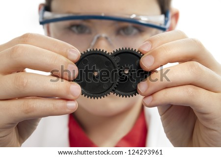 Boy connecting multiple gears while wearing safety glasses, front view. - stock photo