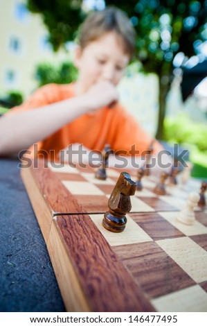 Boy contemplates his next move in a game of chess. - stock photo