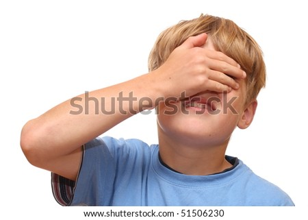 Boy covers hie eyes with his hand - stock photo