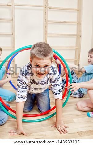 Boy crawling through hula hoops - stock photo