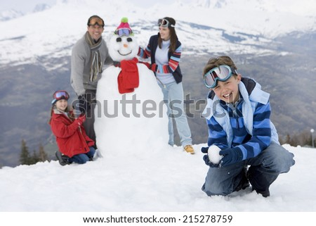 Boy crouching in snow, family by snowman in background, smiling, portrait