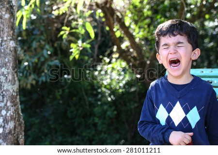 Boy crying while standing up in park - stock photo