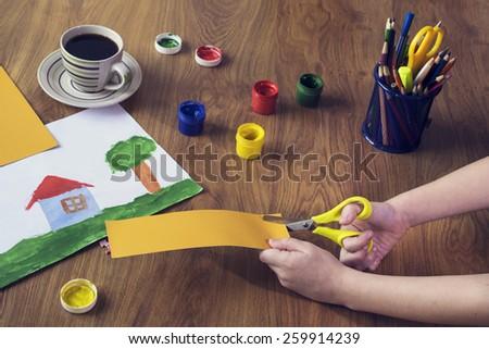 Boy cutting cardboard shape in class - stock photo