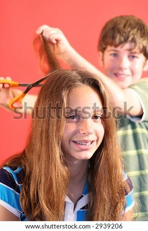 boy cutting girls hair vertical - stock photo