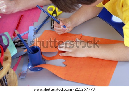 Boy (4-6) cutting shapes out of orange card at desk in classroom, side view, close-up - stock photo