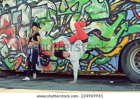 Boy dancing break dance in front of a beautiful girl with stylish bus on the street - stock photo