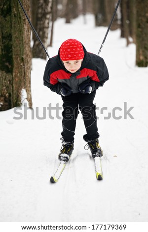 Boy descending from snow hill on skis closeup  - stock photo