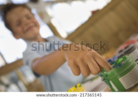 Boy dipping his finger in watercolor paint - stock photo