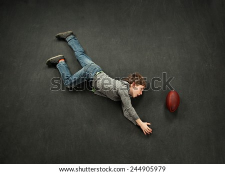 Boy diving for the football catch - stock photo