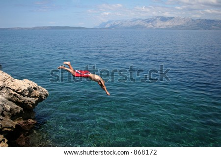 Boy diving from a rock into the sea - stock photo
