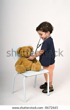 boy doctor examining teddy bear - stock photo