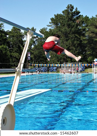 Boy doing a funny jump off the diving board at a public swimming pool. - stock photo