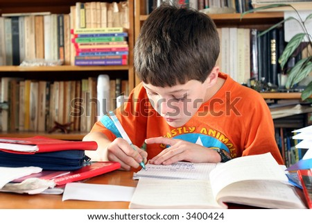 Boy doing a lot of homework at home - stock photo
