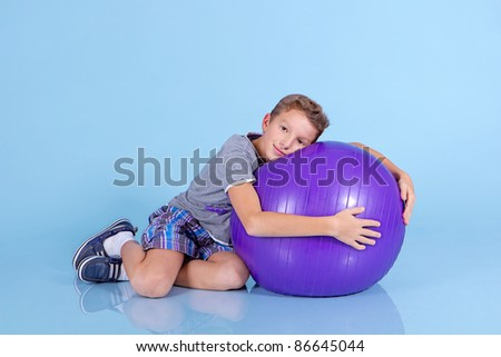 Boy doing gymnastic exercises with a large rubber ball - stock photo