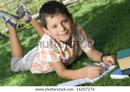 Boy doing home work outdoors - stock photo