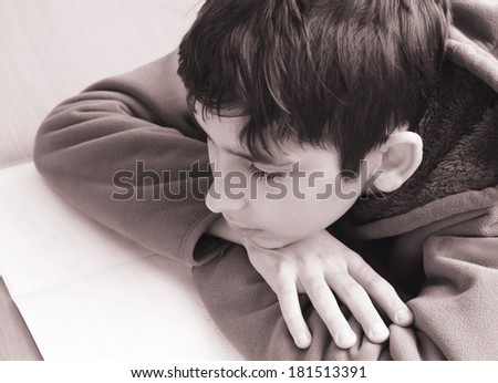 boy doing homework and looks on the writing-book - stock photo
