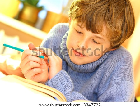 Boy doing homework on bed in sunny bedroom - stock photo
