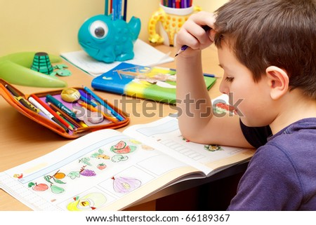 boy doing homework  with color pencil, painting fruits - stock photo