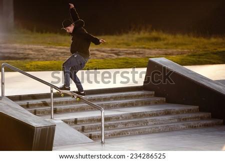Boy doing skateboard trick in skatepark - stock photo