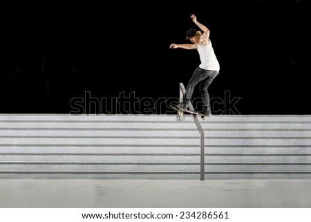 Boy doing skateboard trick on rail - stock photo
