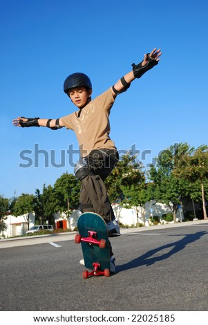 Boy doing stunts on a skateboard in afternoon sun with blue sky in the background - stock photo