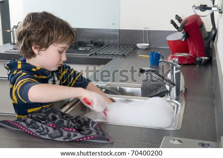 Boy doing the dishes in a modern kitchen - stock photo