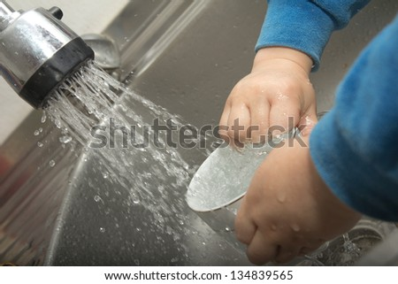 Boy doing the dishes in the sink - stock photo