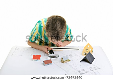 boy drawing and playing with house models on architect's plans - stock photo