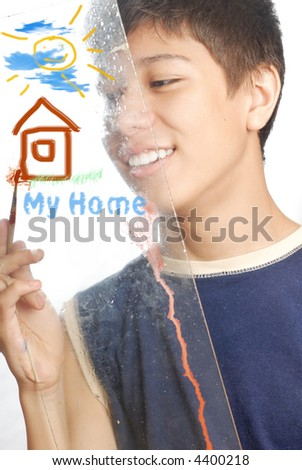 Boy drawing home and sun as a symbols of the family - stock photo