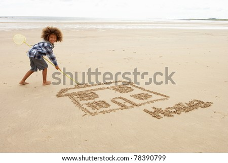 Boy drawing in sand - stock photo