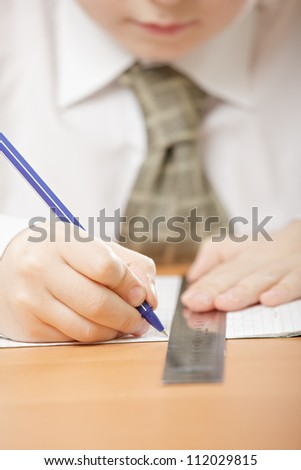 Boy drawing line with metallic ruler