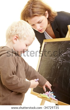 Boy drawing on a blackboard, teacher watching - stock photo