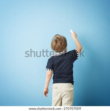 Boy drawing on blank chalkboard - stock photo
