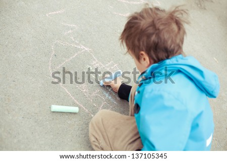 Boy drawing on road. Outdoor. - stock photo