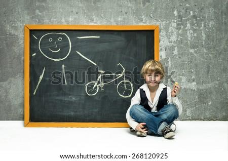 Boy draws bicycle on the blackboard - stock photo