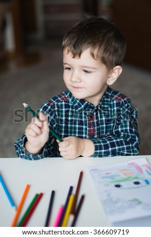 Boy draws with colored pencils