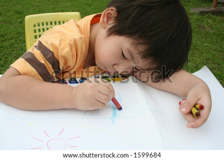 Boy draws with crayon - stock photo