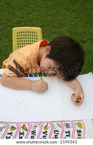 boy draws with crayon on a piece of art paper - stock photo