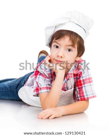 boy dressed as a cook lying on white floor - stock photo